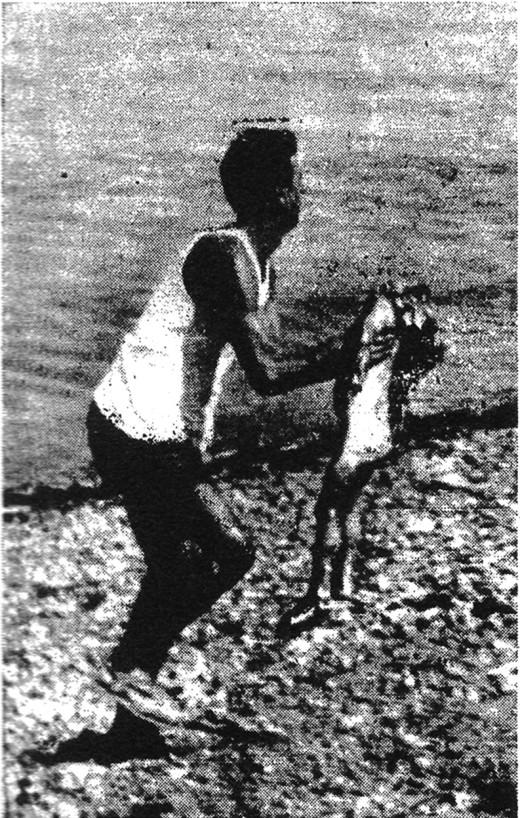 Un soccorritore corre sulla spiaggia con in braccio una bambina colpita a morte